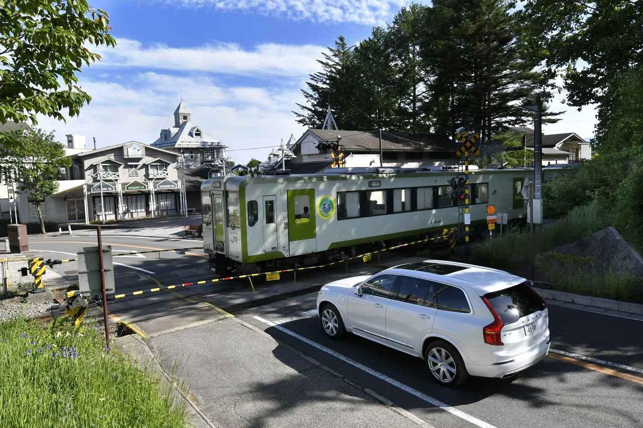 画像: 小海線の清里駅脇にある踏切で列車の通過を待つ。ちなみにこの路線にはハイブリッド鉄道車両キハE200形も運行されているのだが、この時にやってきたのは標準型のディーゼルカーキハ110系の2両編成だった。
