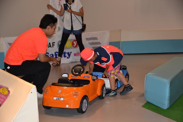 画像: けん引作業の様子。子ども JAF 隊員の制服を着て車両の救助に取り組みます。
