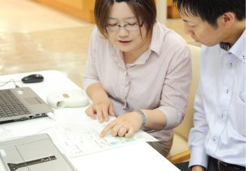 画像: 疲労・ストレス度測定結果の説明を受ける被験者
