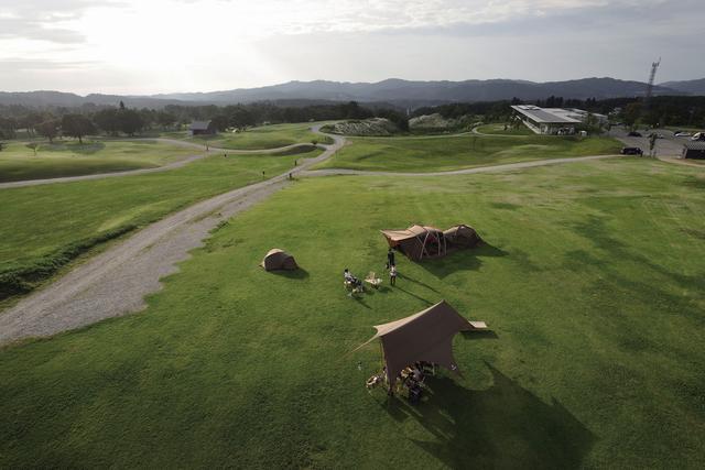 画像: スノーピークの社屋(右奥)を取り囲む広大なキャンプフィールド。一般のユーザーも社員もオートキャンプを楽しめる。山井社長自身、ここでキャンプをしてから出勤することもあるという。