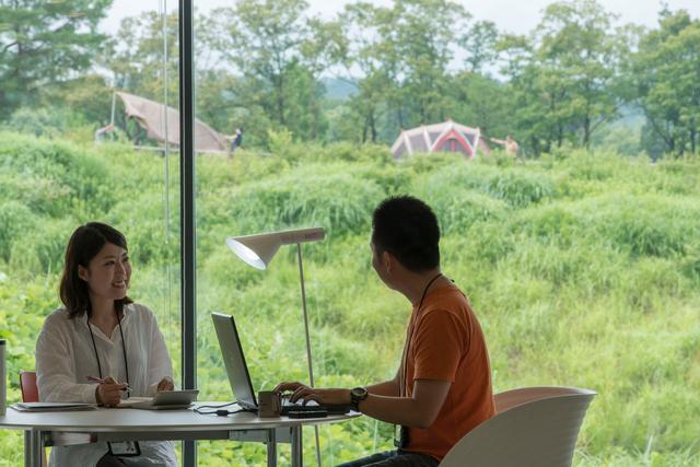 画像: 本社クリエイティブルームにおける仕事の一コマ。窓からはキャンプフィールドが見える。