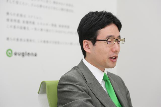 """画像: """"ミドリムシ大使""""を自認する出雲氏。着用するネクタイは常に緑色だ。"""