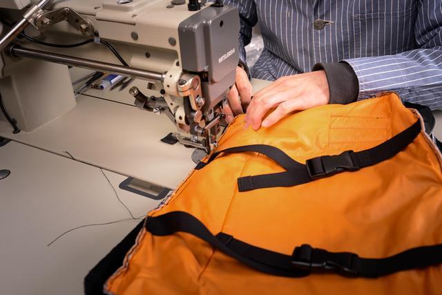 画像: 吉田カバンでは通常、製造元の職人さんに商品修理を依頼するが、廃業してしまった場合や特殊な内容は自社で修理を行う。写真は、TANKERシリーズのオーバーナイターを分解し、縫いまとめ直している様子。ポリエステル綿をナイロン素材で挟んだ3層構造で非常に柔らかい生地のため、縫製には熟練した技術を伴う。TANKERは現在、数カ所の工房で年間約27万本生産されている。