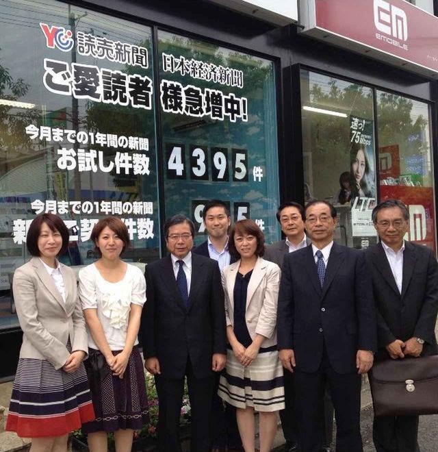 画像: 経営していた新聞販売店の前で撮影した写真。中央後ろが青木氏。