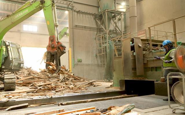 画像: 木材処理の様子。搬入した木材をパワーショベルで運び、右に見える機械に投入して破砕する。