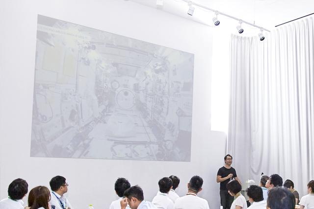 画像: 現在の宇宙船内部の様子を例に挙げ、アイデアのコンセプト検討の肝を語る西村氏。