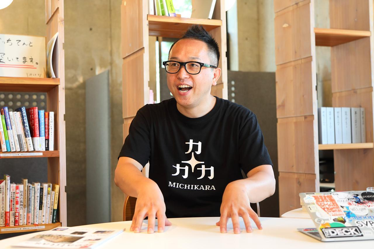 """画像: 山田氏が着ているのは、MICHIKARAのロゴ入りTシャツ。「市民・企業・市役所の3つの力が価値観や立場の違いを乗り越えて協力する」「""""未知から""""新しい価値を生み出す」「""""この道から""""新しい地域・未来をつくる」の3つの意味がMICHIKARAには込められている。"""