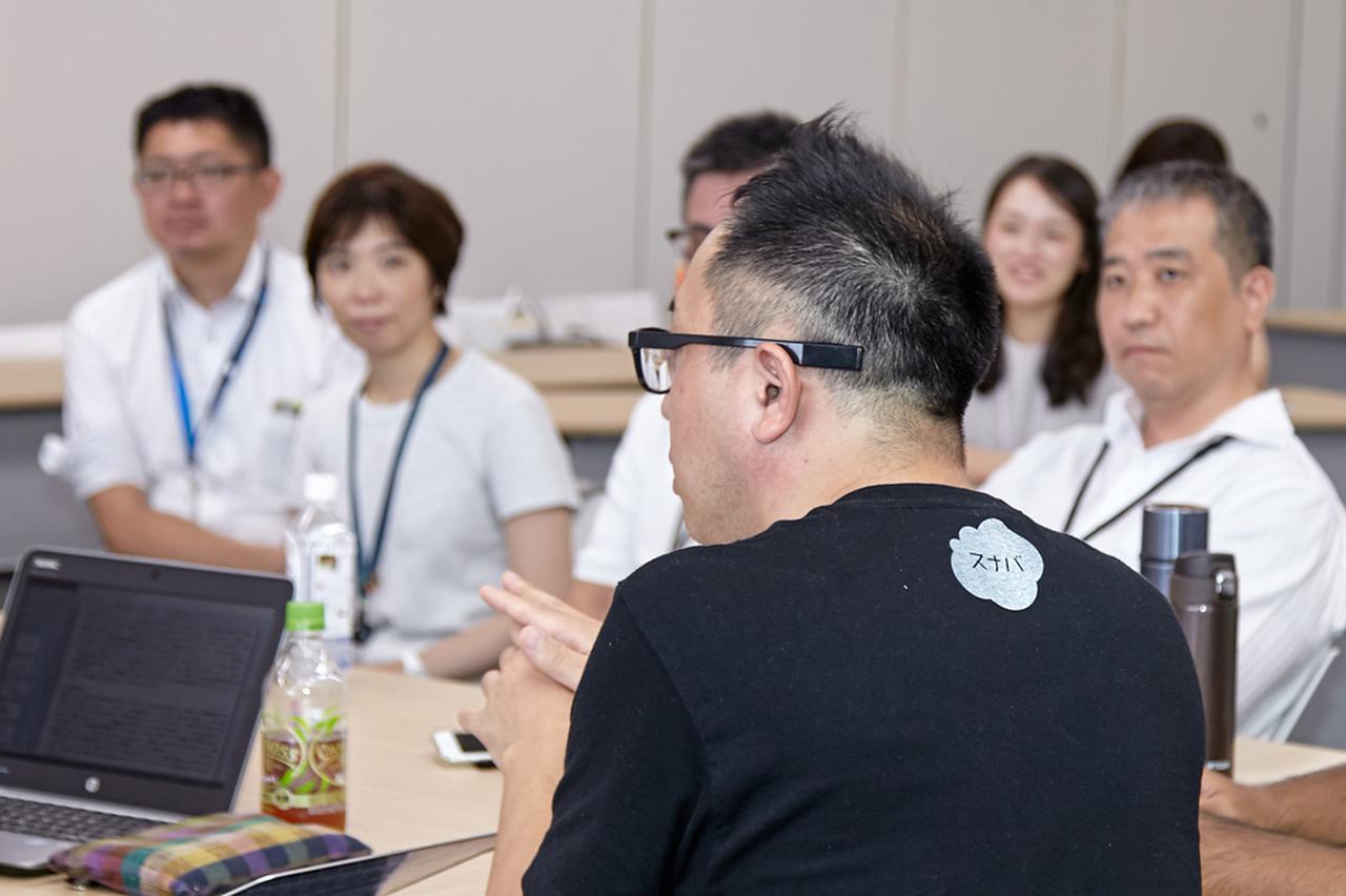 画像: 日立の社員に、アイデアに対するフィードバックをする山田崇氏(手前)。