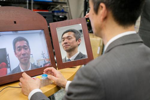 画像: 「扇情的な鏡」の写真 廣瀬研究室の吉田成朗氏が開発した「扇情的な鏡」。普通の表情をしていても、ボタンを押すと微妙に表情が変化する。「悲しいから泣く」のではなく「泣くから悲しい」という感情の揺らぎを実験できる