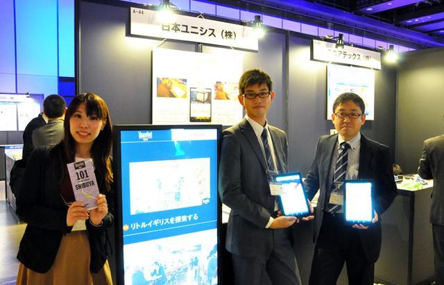 """画像: 日本ユニシスのブースでは、タイムアウト東京社とタイアップしたデジタルサイネージを展示。広告映像を一方的に流すだけでなく、お客さまが行きたい飲食店を現在地からの距離や時間、ジャンルなどで絞り込みながら検索ができるインタラクティブな機能を搭載。英語と中国語、韓国語のほか、各地方を多く訪れる外国人観光客の特性にあわせて10か国語以上の言語に対応することもできる。もうひとつ、多言語接客サービス「WaviSaviBavi」も展示。外国人観光客が飲食店に来店した際に、""""日本流""""のスムーズなコミュニケーションが可能になる。""""通""""の食べ方を紹介するといった、お客さまの旅心を満足させる良質なコンテンツも搭載している"""