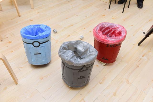 画像: ゴミ箱ロボット:ゴミを見つけると周りの人に近づいていって、ゴミを拾ってくれるように催促する「ゴミ箱ロボット」。手を持たないために自分でゴミを拾うことはできないが、人に助けてもらうことでゴミ拾いを完結させる
