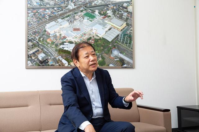 画像: インタビューを受けていただきましたニッケ・タウンパートナーズ株式会社 阪本正一社長。背後の写真は、ニッケコルトンプラザの全体像です。