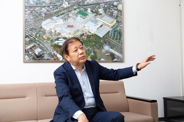 画像: 阪本社長の後ろに飾られているのは、ニッケコルトンプラザ全体の写真です。広大な敷地であることが良く分かります。