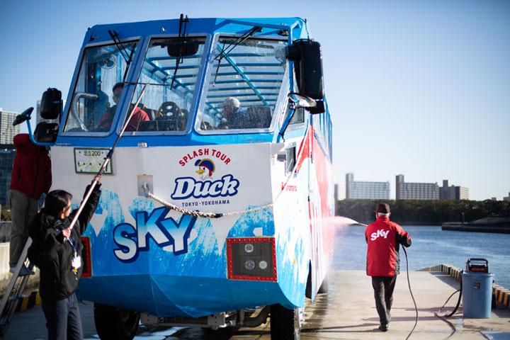 画像: 船からバスへ変身する前に、スロープ脇に待機していたスタッフが、車体を真水のシャワーで洗い流す。さび防止のために毎回行う作業。スカイダックはいろんな人に支えられている
