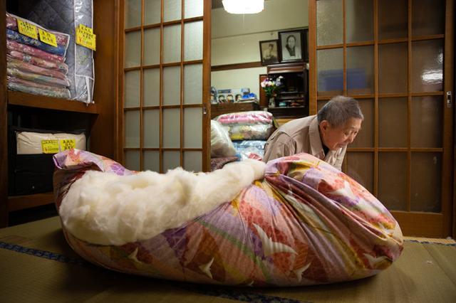 画像: 縦横、何層にも綿を重ね合わせた後で、下ごしらえしておいた布団生地にくるっと丸め込む技はまるで手品。布団と相撲をとっているみたいに見える