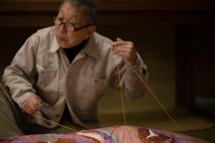 画像: 敷布団の中綿が動かないように、綿と布団側を綴じる。「何千、何万回って針で刺してるから人差し指はもう痛くもかゆくもないよ」