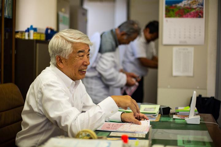 画像: ハチミツ採取を終え、事務仕事をする渡辺哲三さん。8階建ての「トヨスピア」がみつばちプロジェクトの拠点