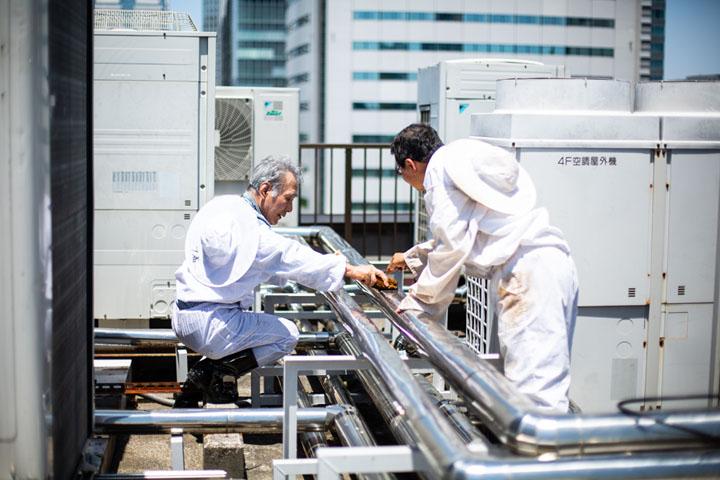 画像: 採蜜が終わると、手際よく遠心分離機や器具を水洗い。場所が屋上のため室外機などの設備もあり、蜜がこびりつかぬよう、念入りに磨く
