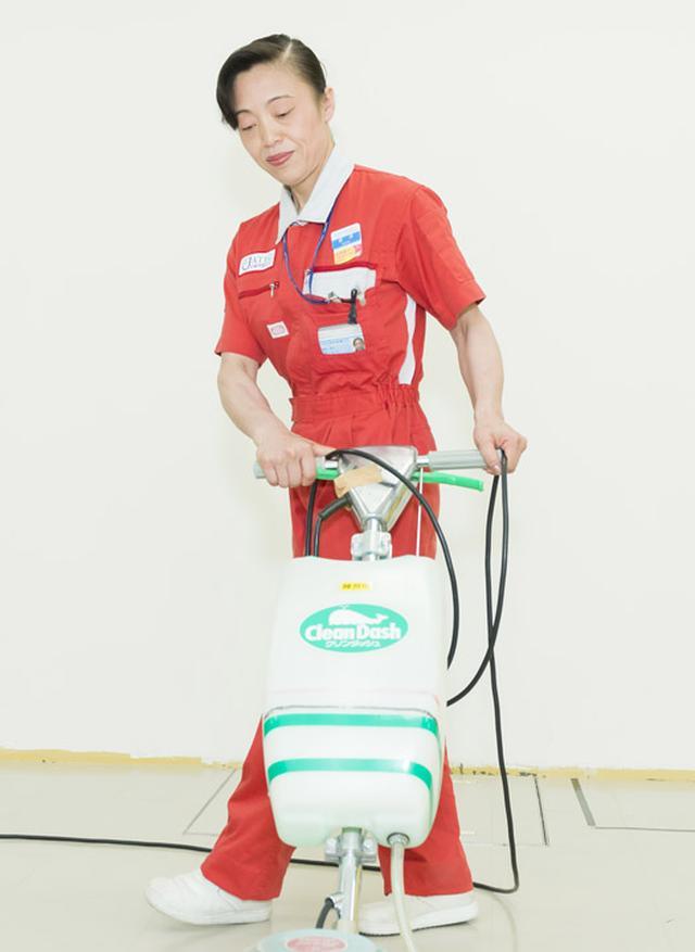 画像: 清掃をしている新津氏 ポリッシャーで床を磨く新津氏。数十キログラムあるポリッシャーを4階まで階段で運ぶこともあるという