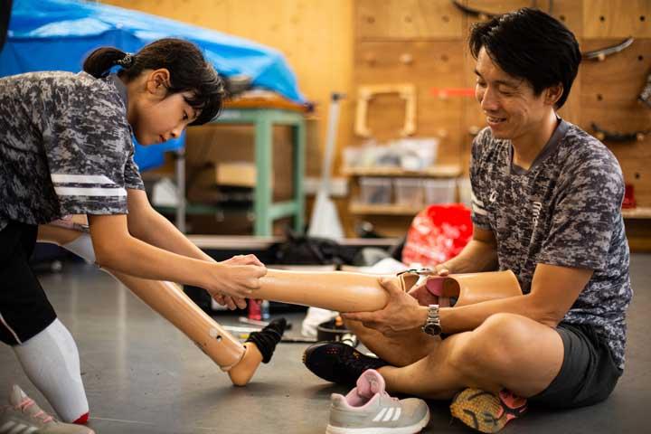 画像: 普段の義足と板バネの履き替えは、沖野さんが調整。一人ずつと向き合って会話する