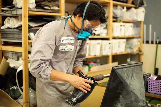 画像: ソケット部分の切削作業をする沖野さん。薬品を使うため防毒マスクをする