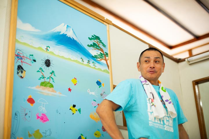 画像: 白山湯3代目の白田 敏博さん 。脱衣所には、ラジオ局のイベントで絵師が描いた富士山と子どもたちが描いた絵が飾ってある