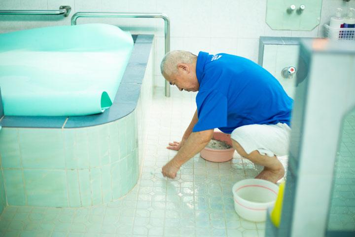 画像: 父の敏郎さんが歯ブラシを使って床のタイルを磨く。驚くほどのスピードで手を動かす