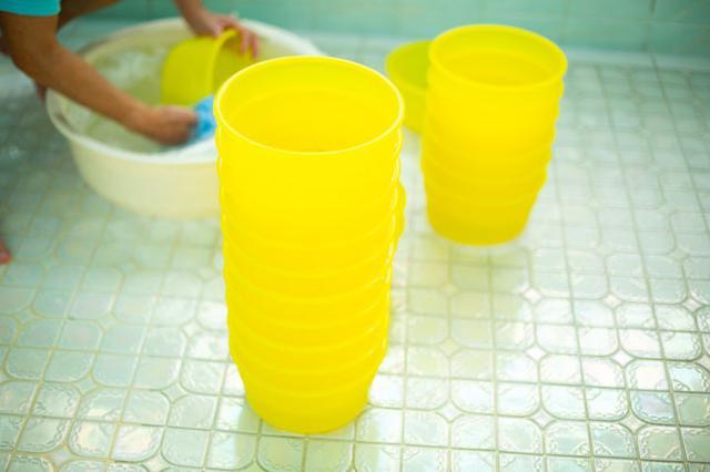 画像: 風呂場の桶や椅子は消毒液のタンクに一晩漬けておき、翌日の営業前に洗い流す