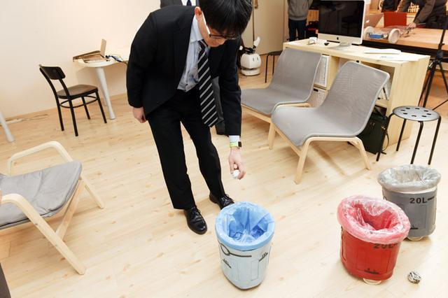 画像: 「わかったよ、仕方ないなー」と、人間がついついごみを拾いたくなるような「場」をロボットが作り、ついついゴミを入れているところ