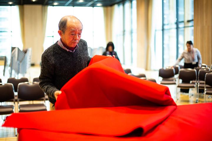 画像: 緋毛氈を使い高座づくりをする小林敬さん。現在は文化センターが用意してくれる専用の台を組み合わせて高さを出している