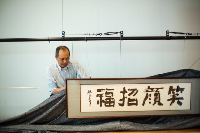 """画像: 「笑顔招福(‶福""""は旧字体)」の書は、日本ユニシス内のかつての部活動「書道部」の先生にお願いしたもの。幕を張り額の位置を整える松嶋安隆さん"""