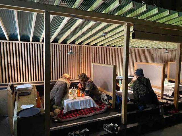 画像: 靴を脱いでコタツでぬくぬくしながら料理を楽しめる。金山さんはお客さんの横に座り込んで、熱心に料理の説明をします