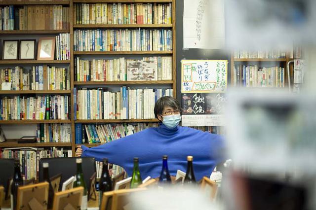 画像: テーブル上は、魚の絵とそれに関連して選んだ日本酒。福地さんのアイデアでユニークな企画展がいつも行われている