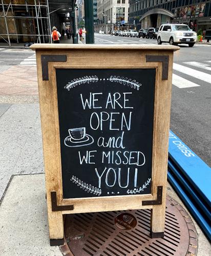 画像: カフェの前の看板。再オープンした店には「We are back(戻ってきたよ)‼︎」という看板が出ていたり、コーヒースタンドの客と店員が「コーヒーが恋しかった。もちろん君のこともね」「なんとか生きのびたよ」と冗談を飛ばしたり