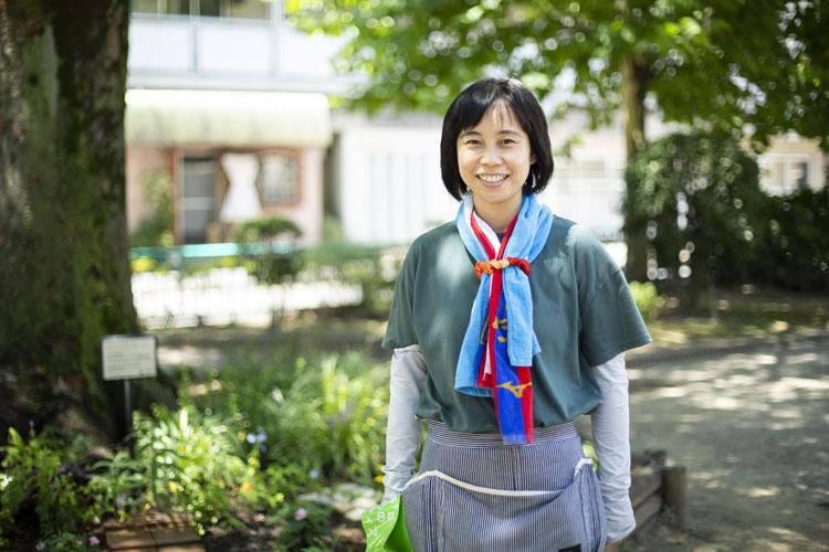 画像: 代表の吉原由美さん。豊洲4丁目公園にある大きなケヤキと花壇は、住民の憩いの場でもある