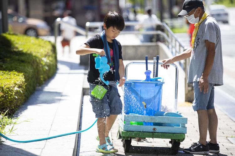 画像: 都道沿いの水やりには、台車と樽が活躍。上畠永靖くんが本日の水番を買って出てくれて、協力先のビルの水道からホースで給水