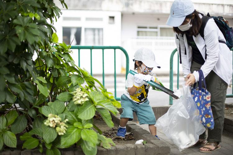 画像: 上手にトングを使って公園内のゴミを拾う高岡凌大くん親子