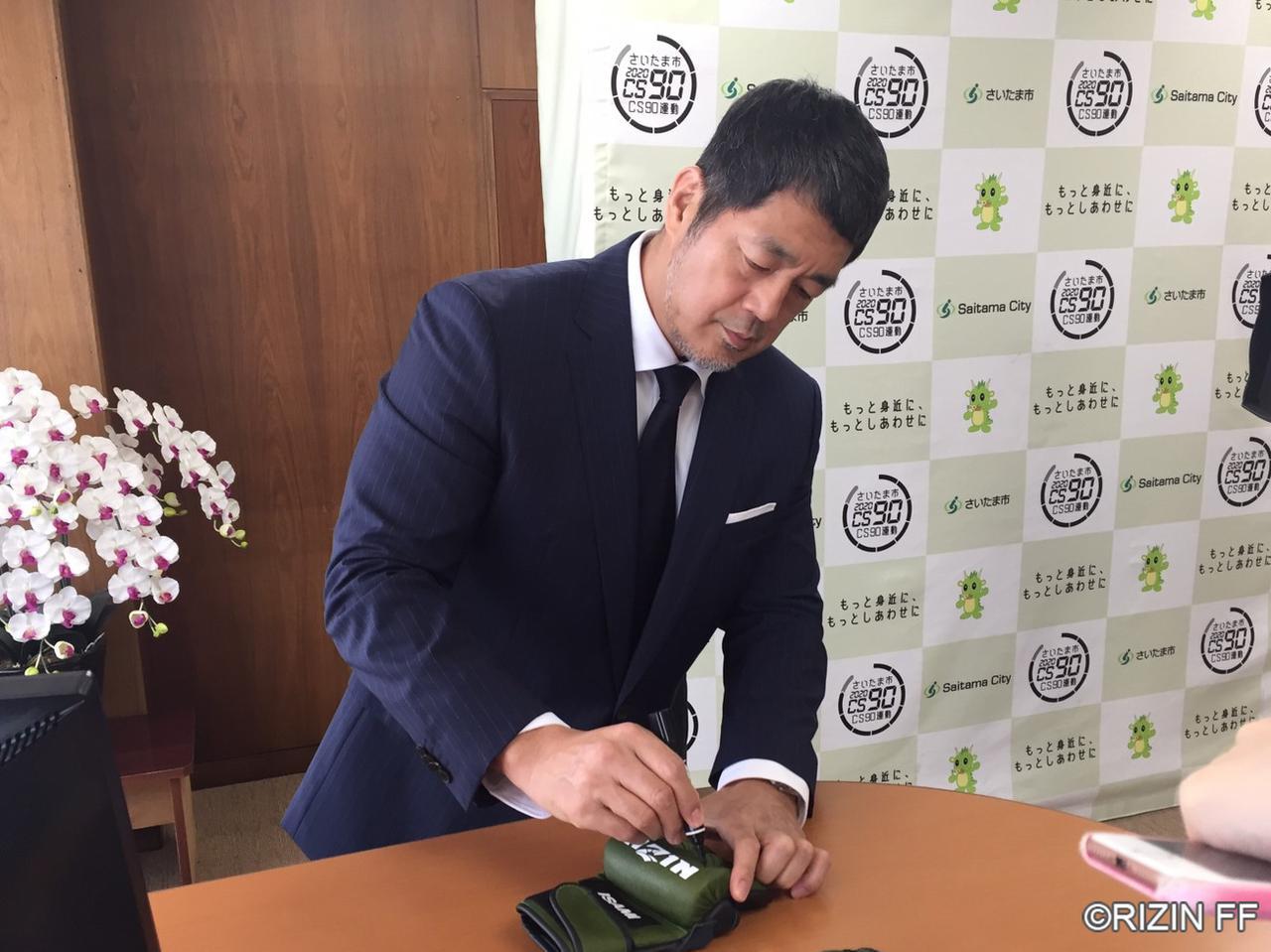 画像: RIZINグローブにサインを入れて清水勇人市長にプレゼント