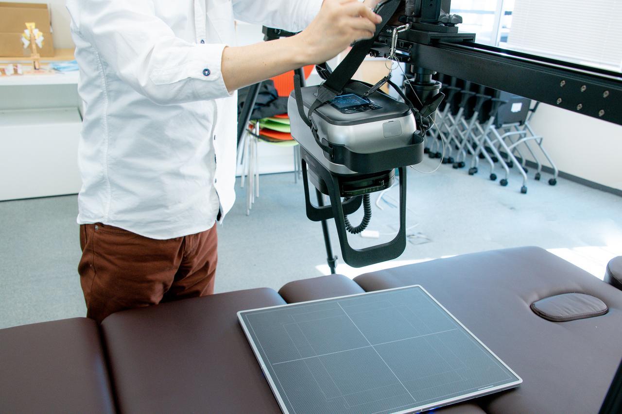 画像: ベッドに置かれているのが、センサーパネル(カセッテDR「カルネオ スマート」)。このパネルの精度が上がったことで、従来の1/4の放射線量で撮影できるようになり、撮影機本体の小型化も実現したのだそう。