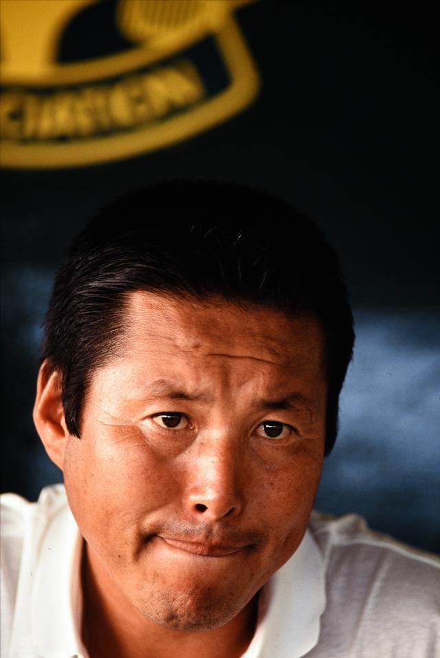 画像: 険しい表情でインタビューに答える尾崎