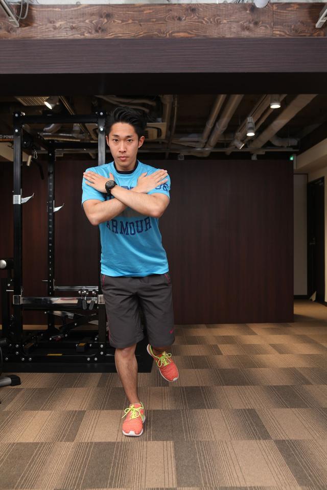 画像: 胸の前で腕を組み、片足に体重を乗せる