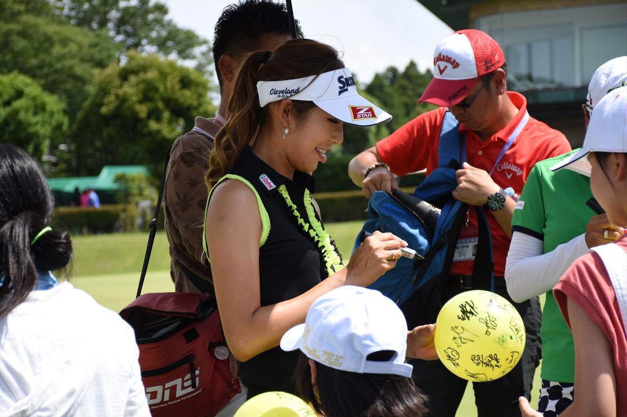画像: ホールアウト後にファンや子供たちに笑顔でサイン