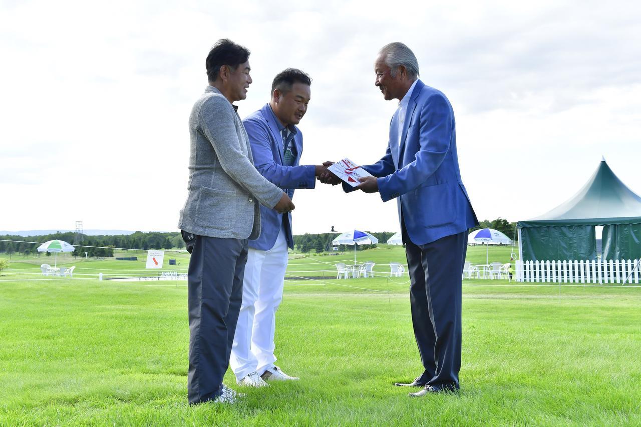 画像: 贈呈時の様子。左から株式会社JOYX前村直昭社長、小田孔明プロ、JGTO青木功会長。