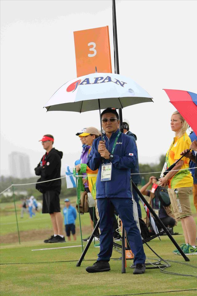 画像: 午前中は傘が手放せなかった。丸山コーチも傘を差しながらの帯同