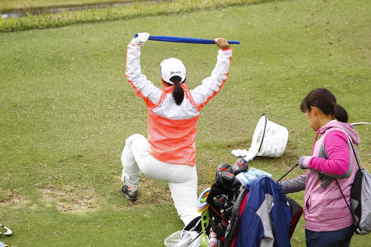 画像: 青いゴムを取り出して、股関節と同時に腕のストレッチ
