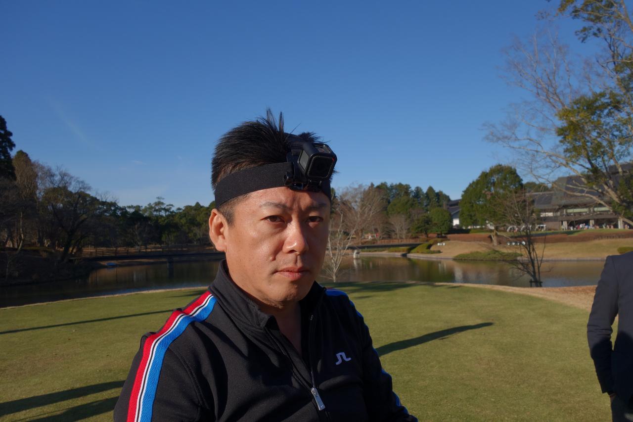 画像: ウェアラブルカメラ「GO PRO」を着用してショットに臨む堀江氏。プロがどのようにボールを見ているか? そんなことも今後のインターネット中継ではライブで見られる、かも