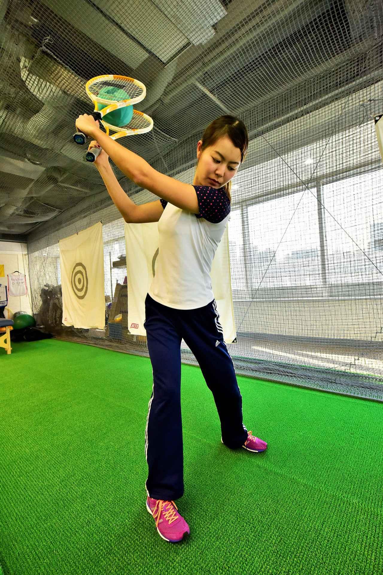 画像: 2本のテニスラケットで挟んだボールを落とさないように素振りを行う