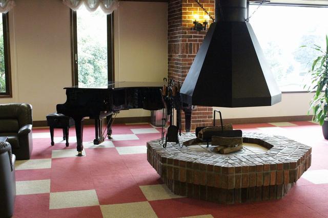 画像: 暖炉とグランドピアノが非日常の空間を演出している