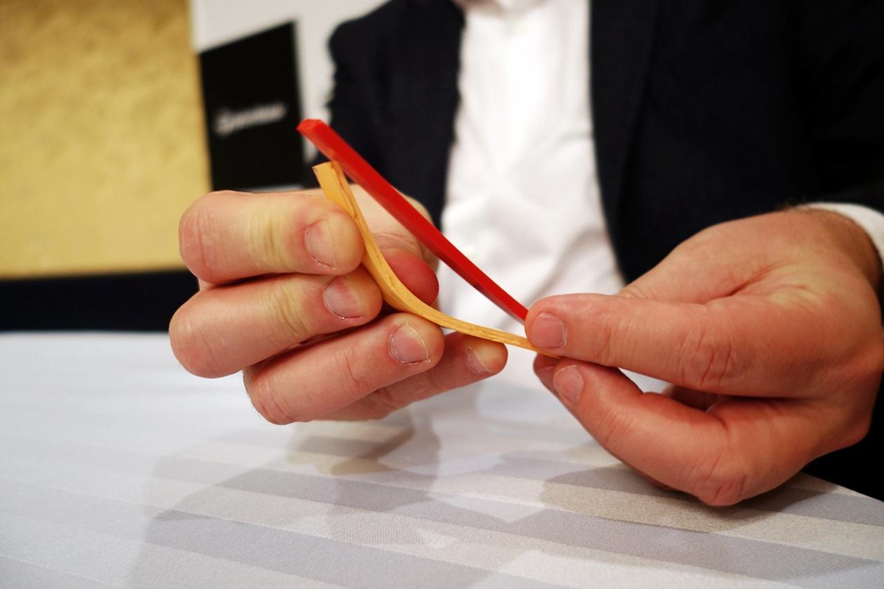 画像: 黄色いゴムは従来の、赤いゴムは「TP5」の弾道イメージ。TP5は、スピン量が少ないことで、めくれ上がる弾道にはならないが、初速が速いことで高さが出ることから、降下角度は大きくなり、結果として止まると説明