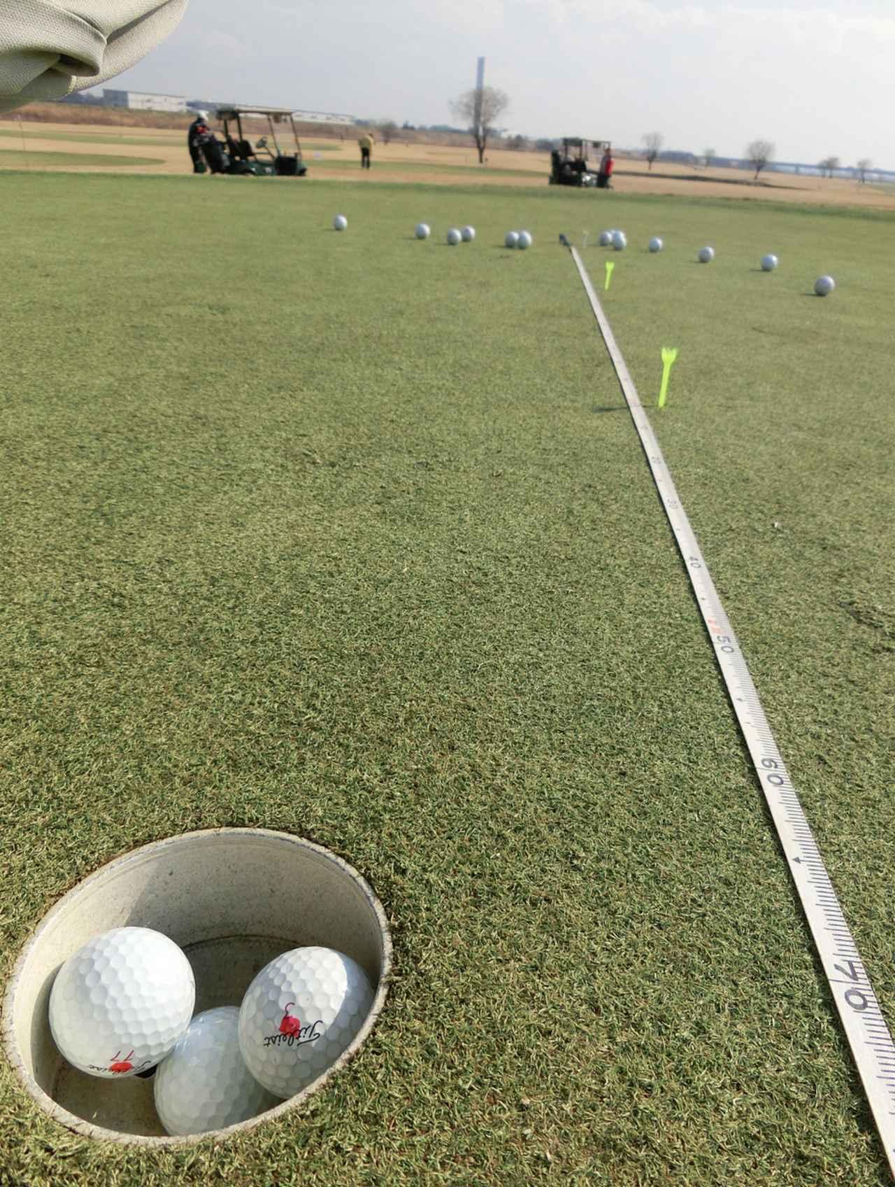 画像: 平地12.5 フィート環境の「下り」平均傾斜2度=(平地で20フィート相当)での実験風景。写真上方14個のボールはカップに触れなかったためカップを2.7メートルオーバーしたもの。カップインしている3個のボールはオーバーしたボールと同じ強さだったが、カップど真ん中を通過しようとしたのでカップインした。